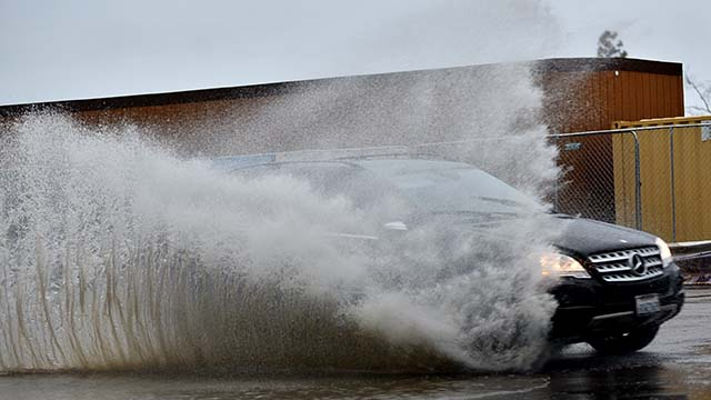 A car splashes through standing water on Pacific Highway.