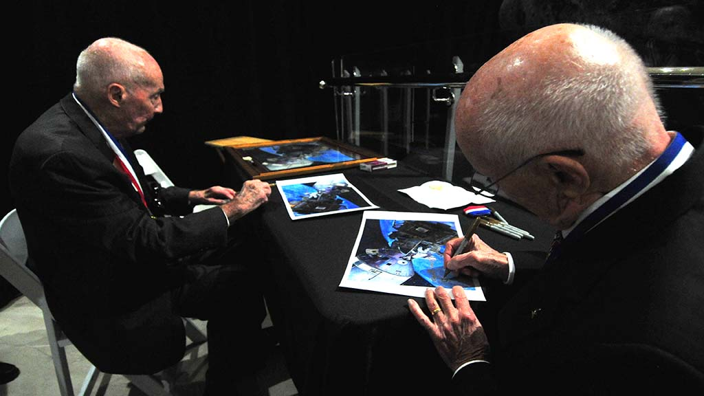 Jim McDivitt (left) and Gerry Griffin autograph photos from Apollo 9 mission that proved docking and other maneuvers could be done in Apollo 11.