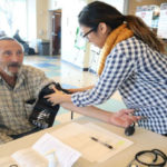 Checking a senior citizen's blood pressure