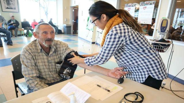 Checking a senior citizen's blood pressure