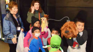 Paula Sassi and Mimi Pollack with immigrant children at the San Diego Greyhound station.