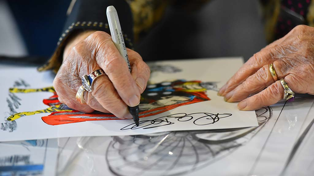 Allen Bellman, a former Marvel artist, signs a poster with one of his drawings.