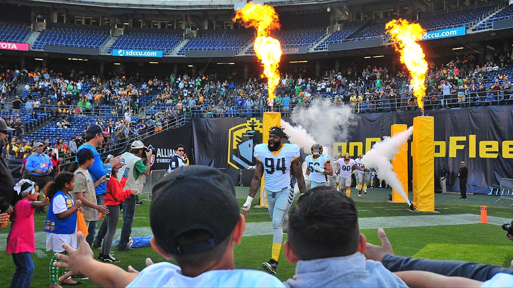 Fleet defensive end Damontre Moore heads toward children's outstretched hands during introductions.