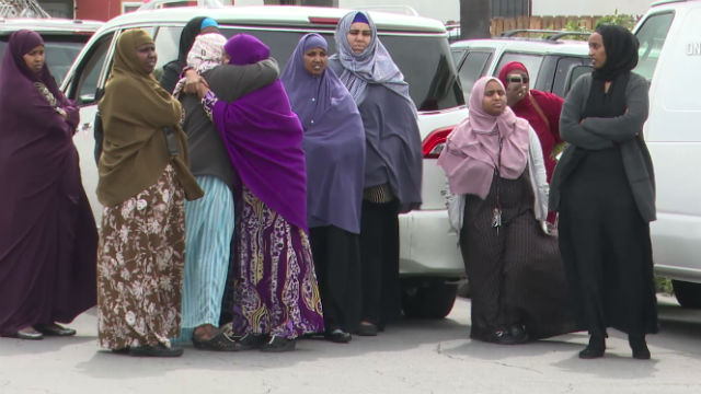 Members of the Somali community gather at the crime scene