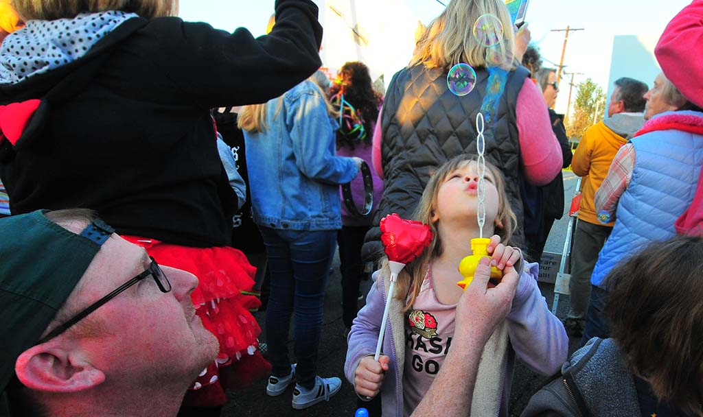 "Peter Kinnally of Alpine and his daughters blow soap bubbles during the ""Rainbow Dance Party"" to oppose"