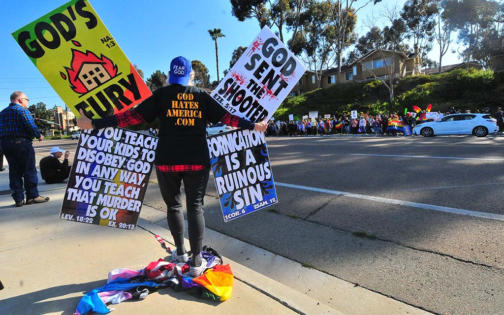 Shirley Phelps-Roper stands on an American flag and LGBT pride flags as she spreads the Westboro Baptist Church message.