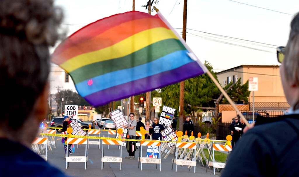 Counter protestors fly rainbow flags as three members of Westboro Baptist Church protest in a penned off area in front of El Cajon Valley High School.