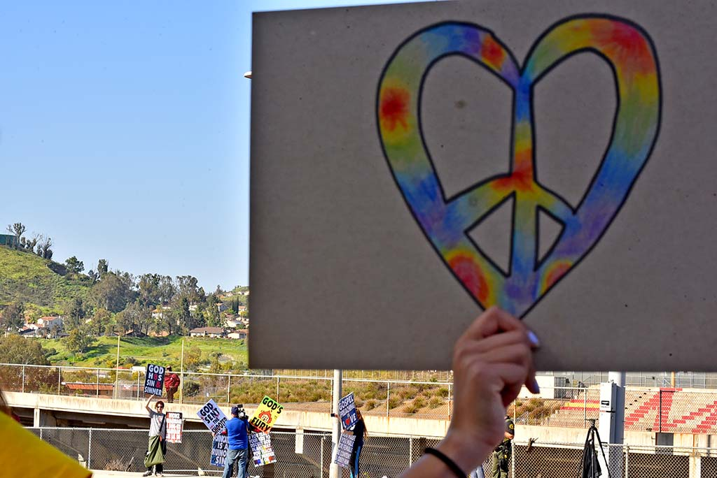 A counter protestor holds a rainbow peace heart as Westboro Baptist Church members display ant-gay signs across the street.