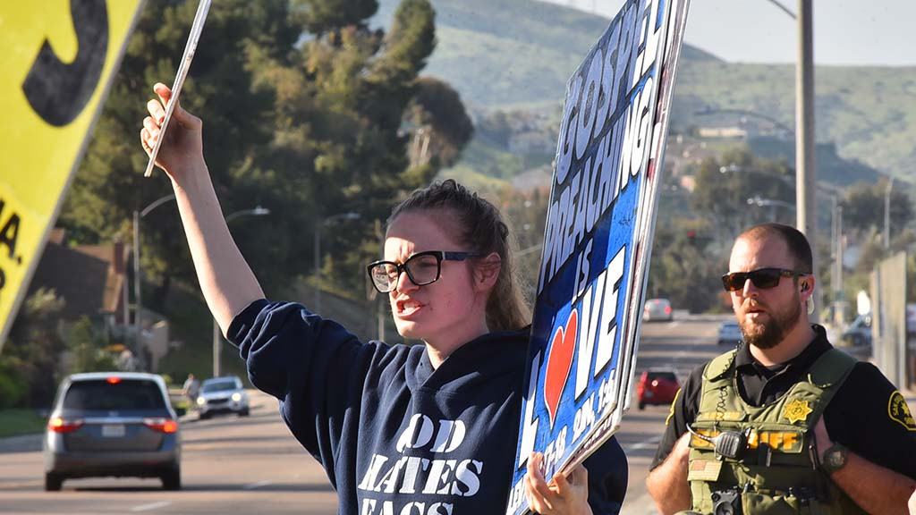 Rebekah Phelps-Roper of Westboro Baptist Church displays signs and signs to recorded music in front o Monte Vista High School.