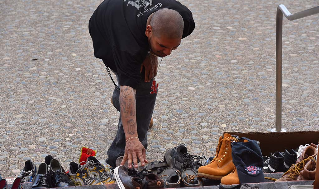 Clients at San Diego Rescue Mission lay shoes representing 111 homeless people who died in the county last year.