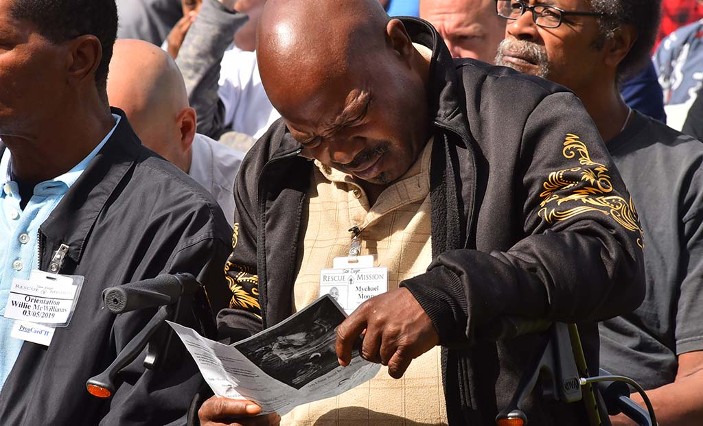Mychael Moore of the San Diego Rescue Mission looks over the program for the prayer vigil at Waterfront Park in downtown San Diego.