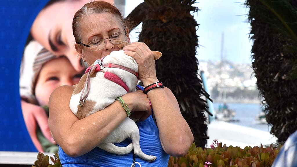 Stefanie (who didn't want to give her last name) of the San Diego Rescue Mission hugs her dog during the prayer vigil.