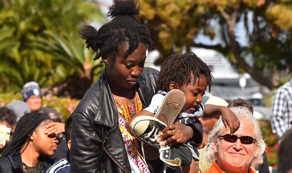 A woman and her child process forward to place shoes on the steps of the County Administration Center.