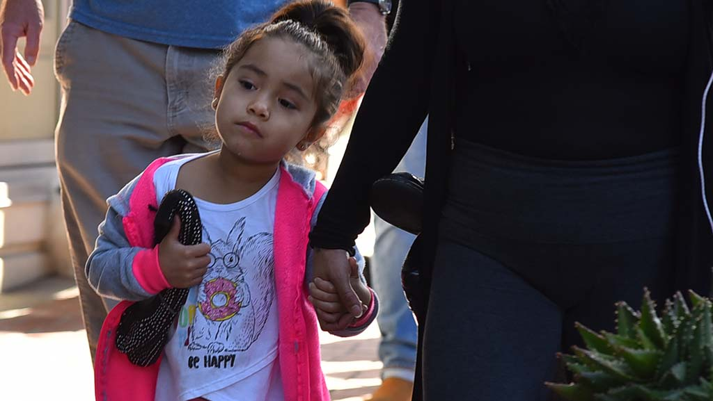 A little girl and her mother walk downtown carrying shoes to symbolize homeless people who have died.