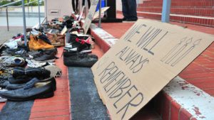 Shoes and cardboard signs serve as reminders of homeless people who died in San Diego County in the past year.