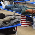 Two young men seeking asylum rest on cots at a former shelter while waiting to begin their journey to their sponsors.