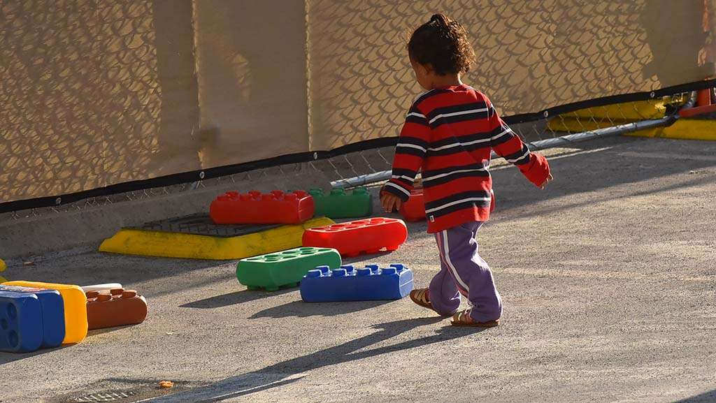 A toddler plays outdoors at the shelter while his family waits for further travel.