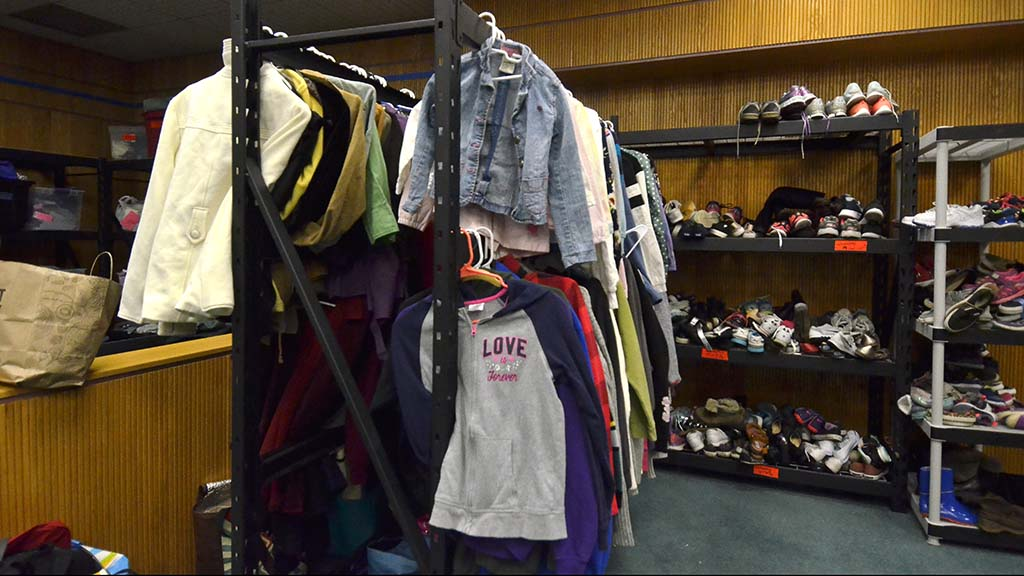 As asylum seekers arrive at the shelter, they are fitted with donated clothes.