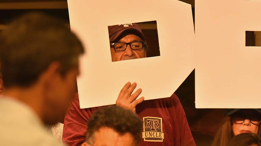 """A Beto O'Rourke supporter peers out from behind the letter """"B"""" at a town hall gathering."""