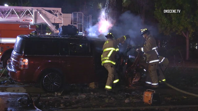 Firefighters battle flames from car