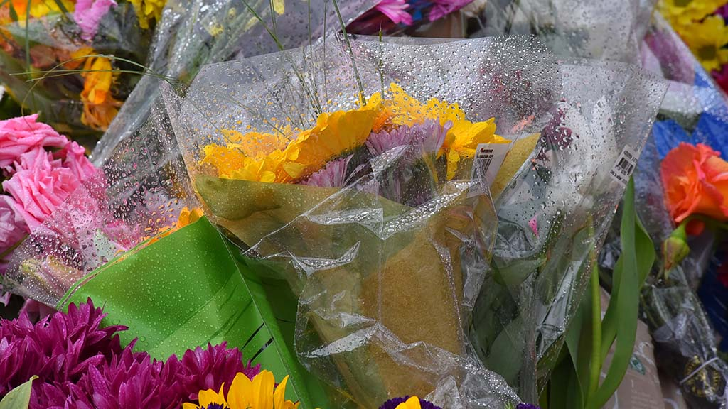 Light rain fell on bouquets of flowers left at a memorial across the street from the synagogue in Poway.