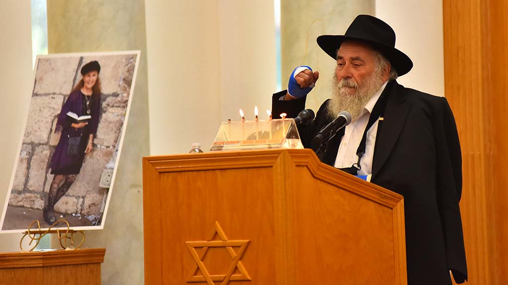 Rabbi Yisroel Goldstein of Chabad of Poway expresses his resolve next to a photo of Lori Kaye.