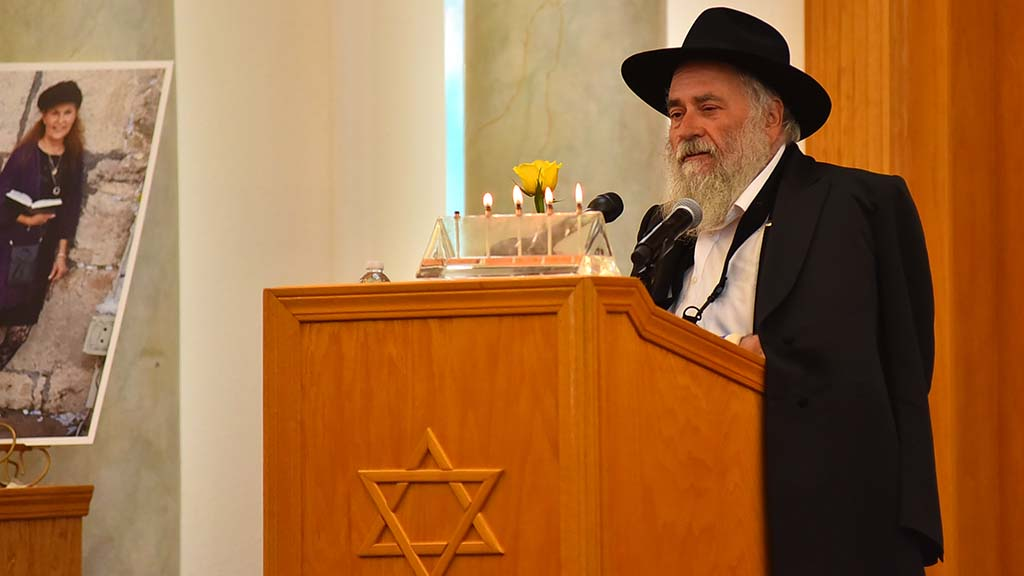 Rabbi Yisroel Goldstein of Chabad of Poway holds a yellow rose to symbolize Lori Kaye's generosity.