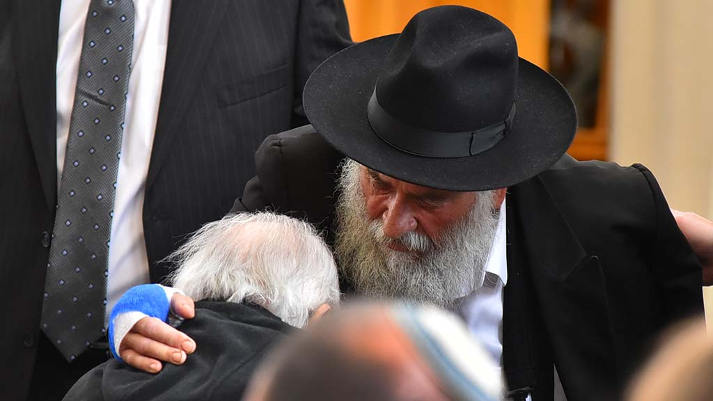 Rabbi Yisroel Goldstein consoles Richard S. Gilbert, father of Lori Kaye before the service.