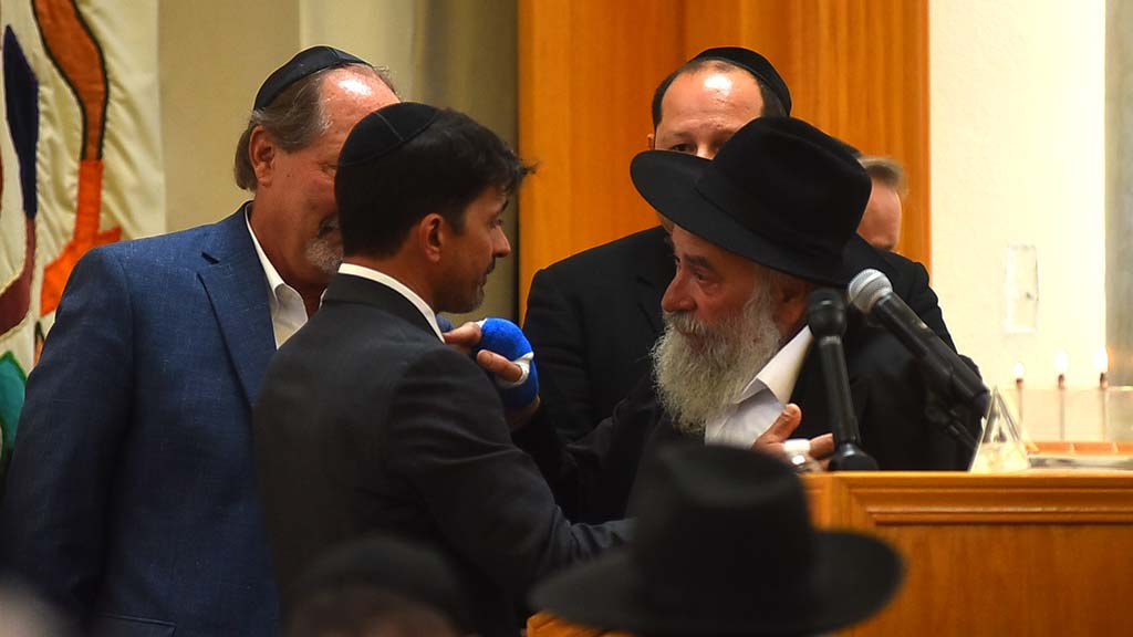 Rabbi Yisroel Goldstein speaks with Oscar Stewart who is credited with being a hero for chasing the gunman out of the synagogue.