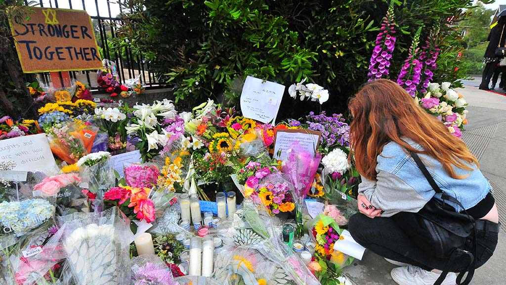 A young woman pauses in front of the floral memorial in front of Chabad of Poway.