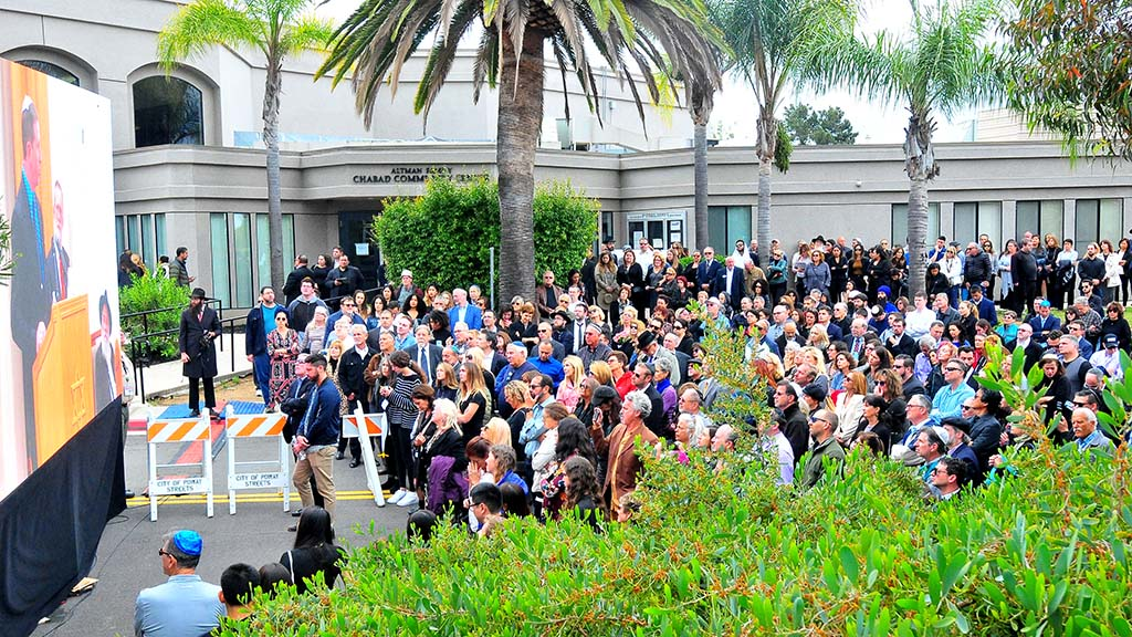 More than 100 people stood in a road alongside the synagogue to watch a close circuit viewing of Lori Kaye's funeral in Poway.