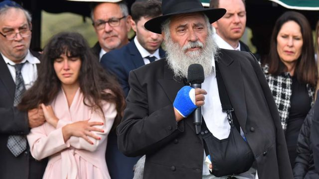 Chabad of Poway Rabbi Yisroel Goldstein speaks to those gathered at the gravesite of Lori Kaye at El Camino Memorial Cemetery.