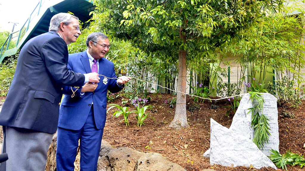 Douglas Myers, CEO of San Diego Zoo Global and Chinese Consul General Zhang Ping unveil a plaque near a tree to recognize the countries' friendship.