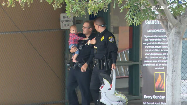 Police officers carry the toddler