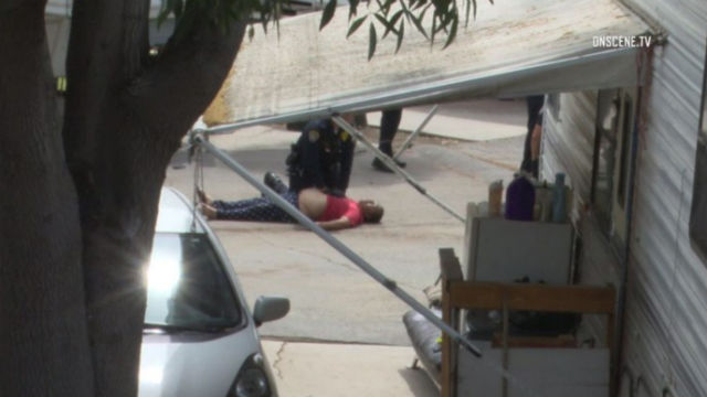 Police officer examines shooting suspect