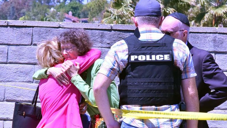 Women walking away from Chabad of Poway on Rancho Bernardo hug.