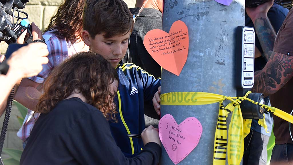 Two children put up hearts on a light pole across the street from Chabad of Poway.