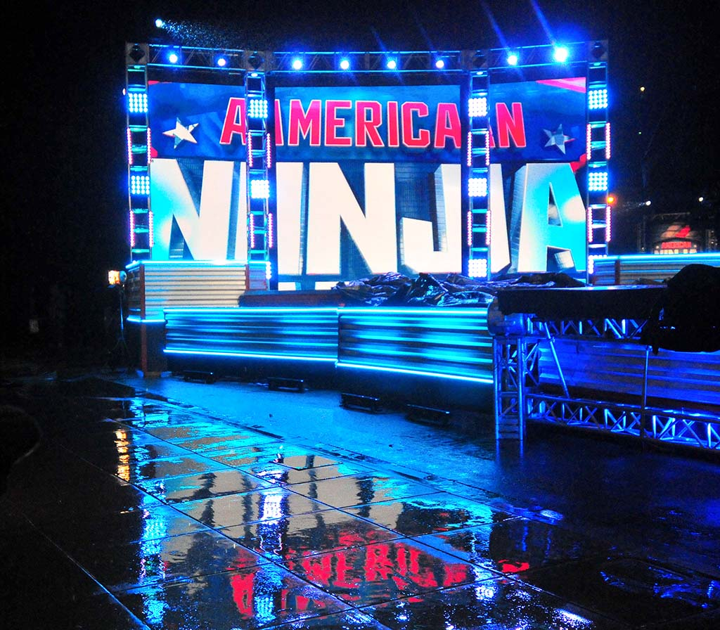 """During a rain delay, the ANW logo is reflected on the wet pavement of a set once used for """"Back to the Future."""""""