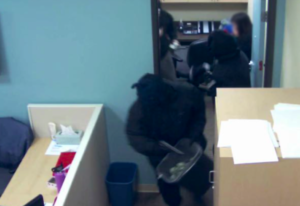 Bank employee at upper right watches as masked bandits grab trash bins to hold cash.
