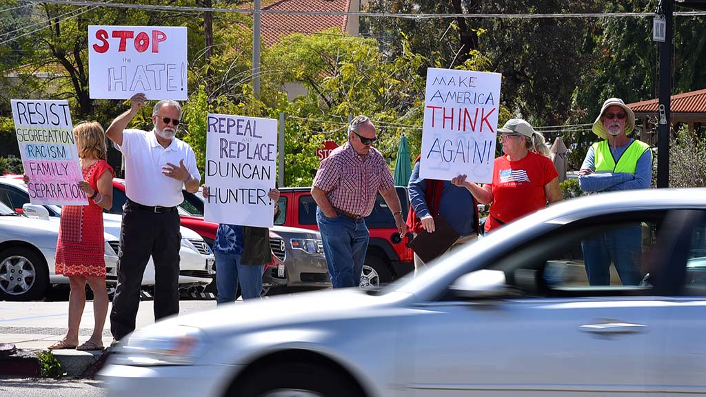 A handful of protesters display signs to cars going past Ramona Mainstage, where current and former congressmen Duncan D. and Duncan L. Hunter were set to speak.