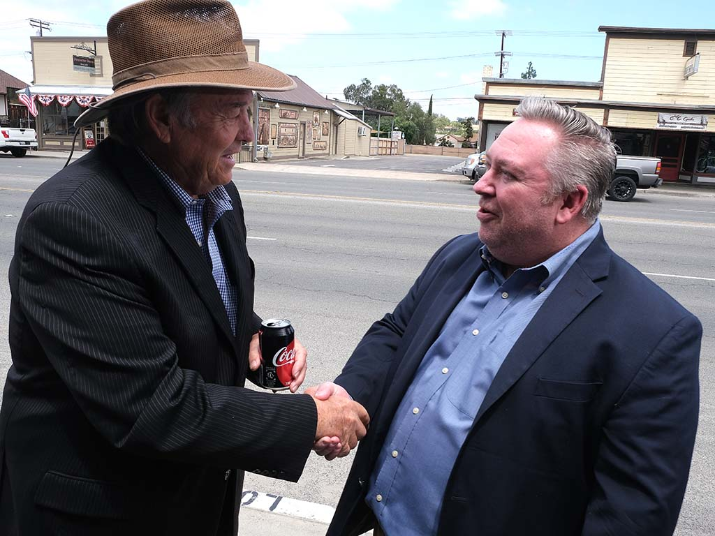 Former Rep. Duncan Lee Hunter greets Ramona resident Mike Harrison, deputy chief of staff for Duncan D. Hunter.