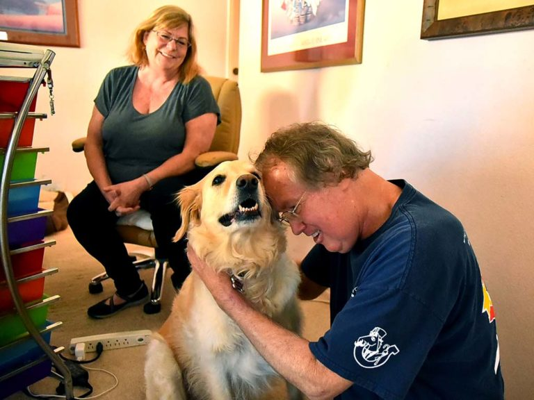 Max Branscomb communes with his golden retriever Leilani at home in Bonita with his longtime journalist wife Leslie looking on.