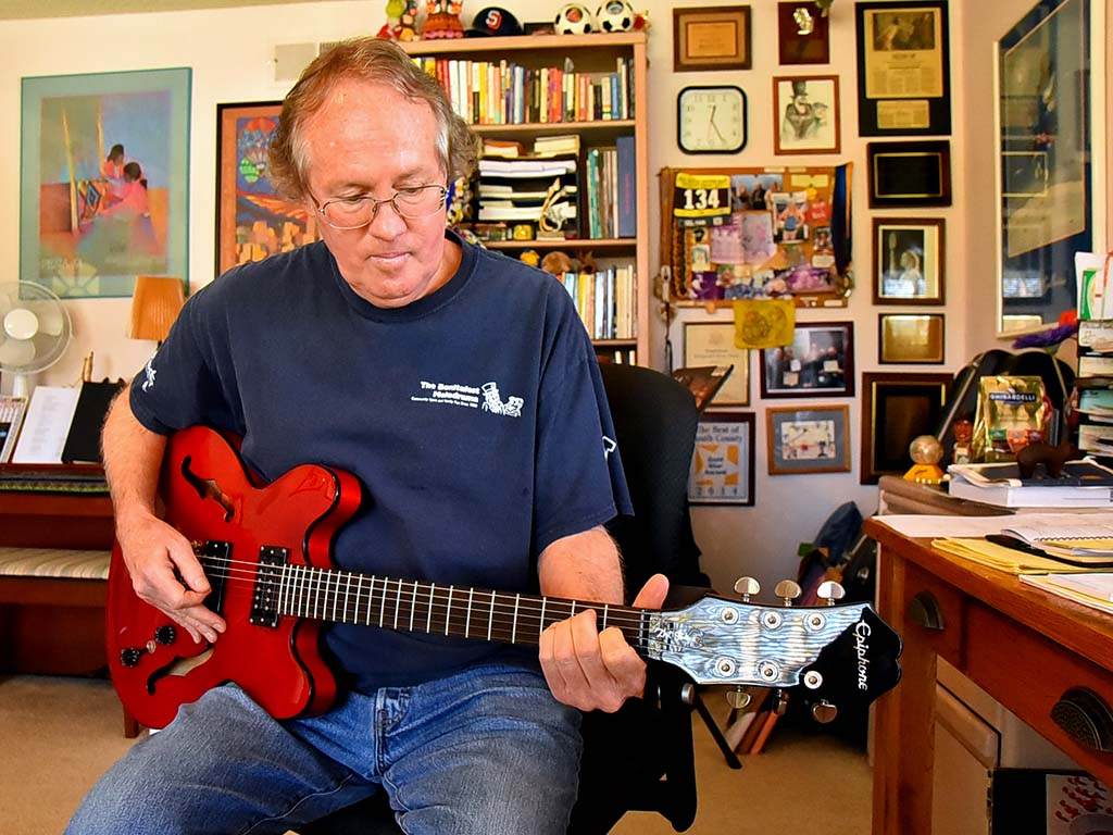 Max Branscomb plays guitar in the study of his Bonita home.