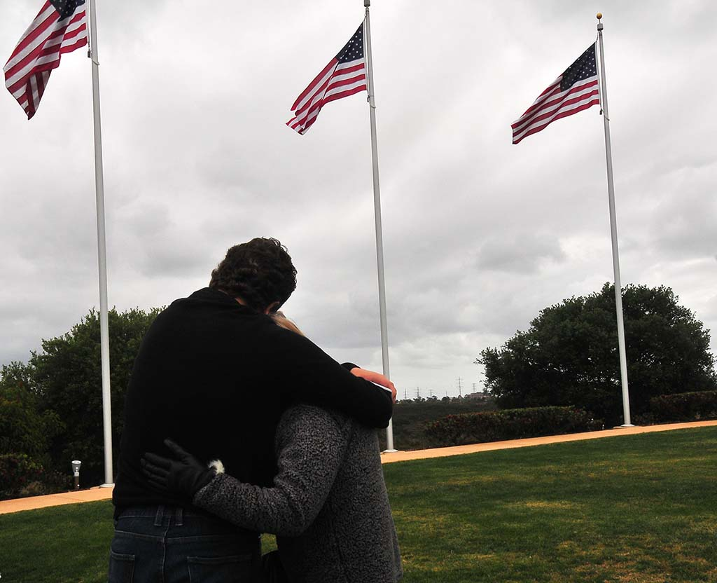 A young man comforts a woman after the Memorial Day event at Miramar National Cemetery.