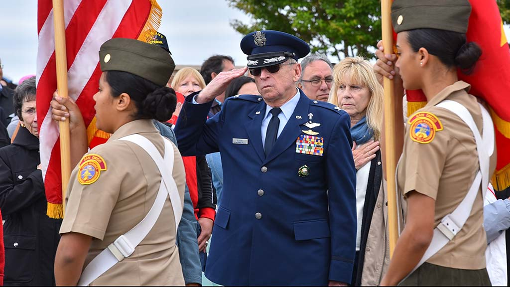 Lt. Col. Rick Blank, deputy command chaplain for the California State Military Reserve, salutes the American flag as the colors are retired.