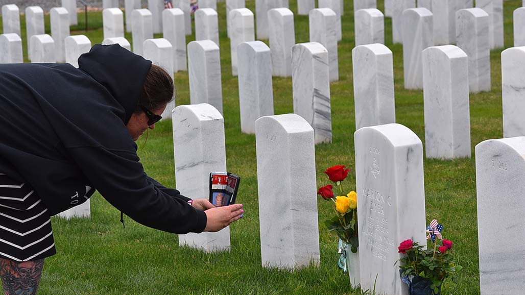 Charlyn Rodgers of San Diego takes photos of headstone of her grandmother, Marion G. Dyer, whose husband was a major in the U.S. Marine Corps.