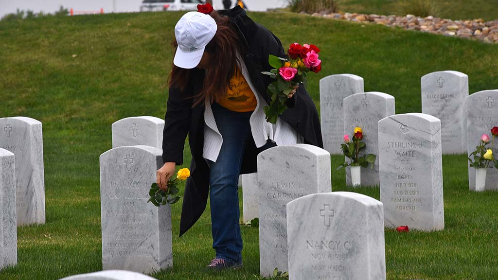Kathy Anderson-Gobby leaves flowers from Forever Grateful of Ramona on graves on Sunday at Miramar National Cemetery.