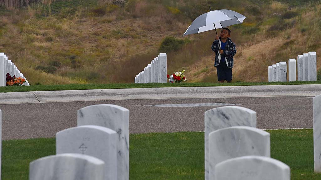 A young boy with a family member nearby visits the Miramar National Cemetery on a drizzly Sunday afternoon.
