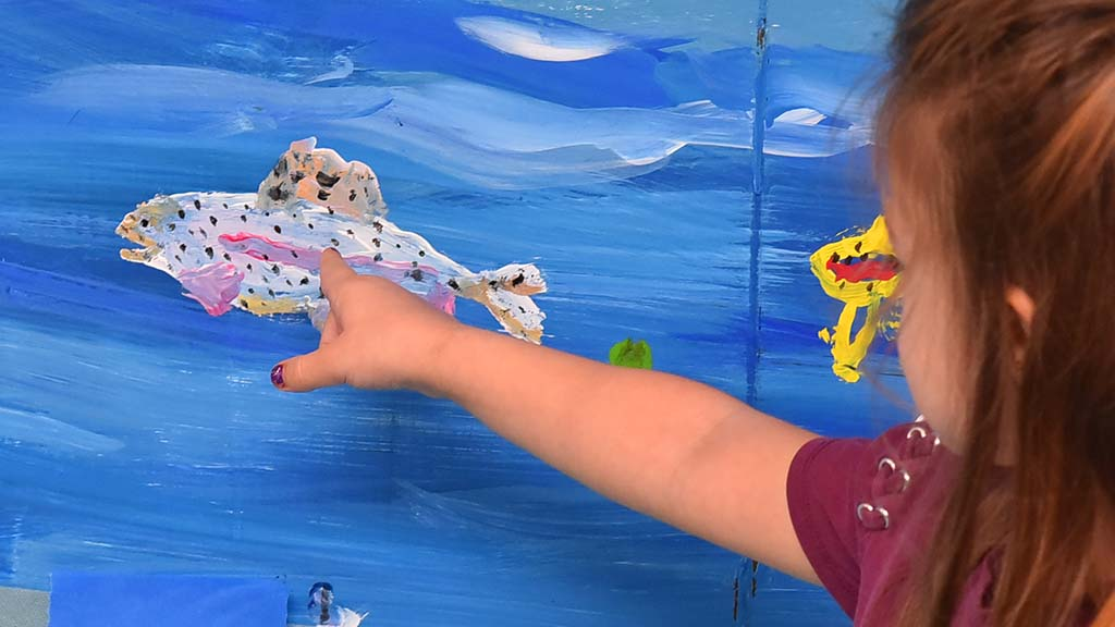 Granddaughter Harley, 4, shows off the fish she and her grandmother, Debbie Patenaude, of Santee painted.