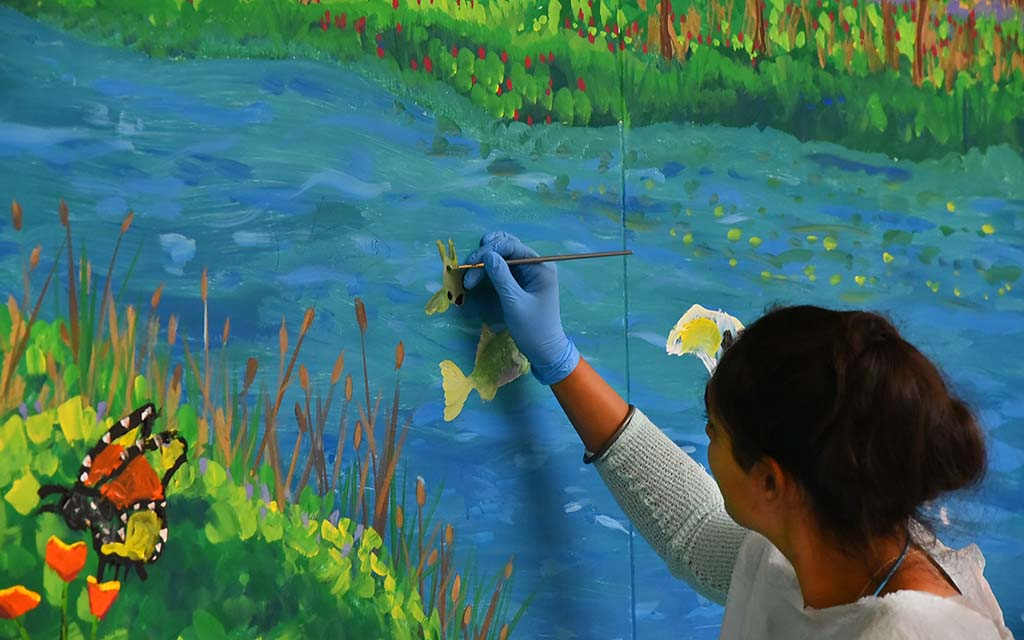 Volunteer Ravleen Khalsa-Basra skillfully added fish to the river scene at Parkway Plaza in El Cajon.